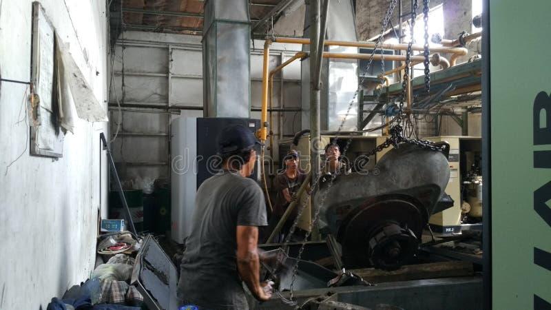 Les travailleurs réparent de l'outillage industriel qui éprouve des dommages graves Réparation des moteurs de compresseur photographie stock libre de droits