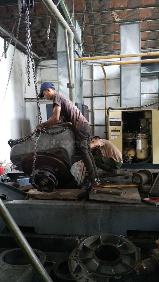Les travailleurs réparent de l'outillage industriel qui éprouve des dommages graves Réparation des moteurs de compresseur photo libre de droits