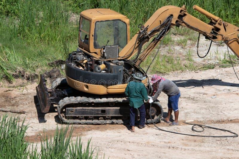 Les travailleurs réparent le seau de bouteur à l'extérieur photos stock