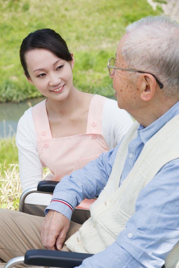 Les travailleurs sociaux et l'aîné japonais parlent dans le domaine images stock