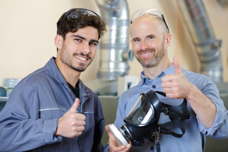 Les travailleurs tenant le masque avec des toxines filtrent renoncer à des pouces image stock