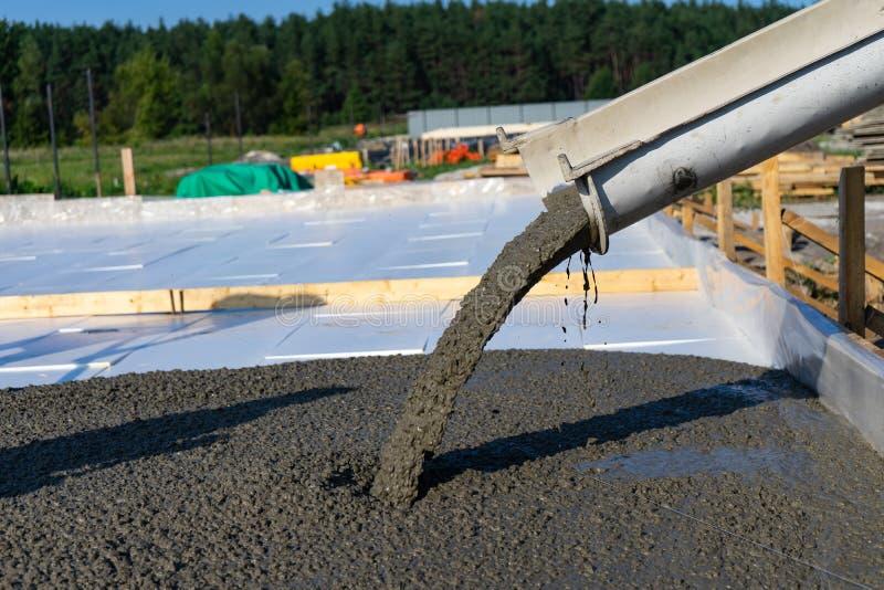 Les travailleurs versent la base pour la construction d'un bâtiment résidentiel utilisant les mélangeurs concrets mobiles photographie stock libre de droits