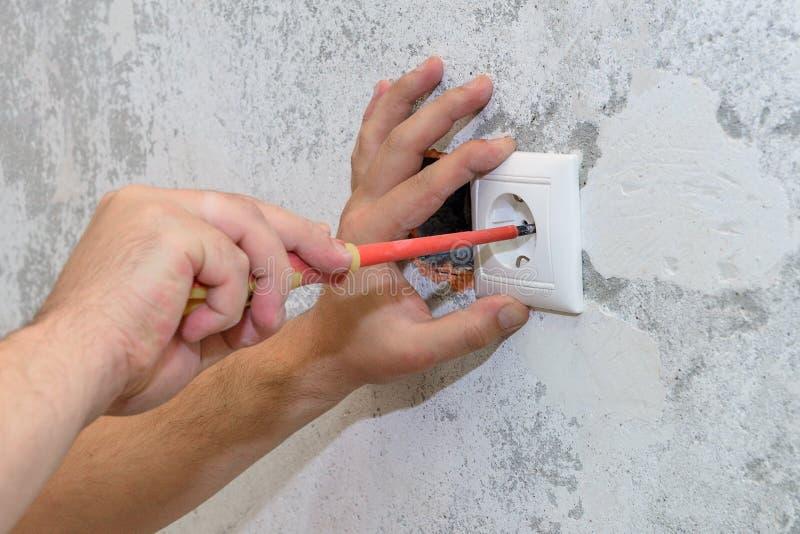 Les travaux de construction, l'électricien installent la prise images stock