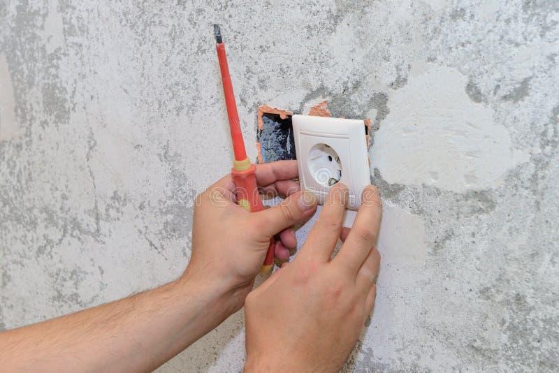Les travaux de construction, l'électricien installent la prise photo libre de droits