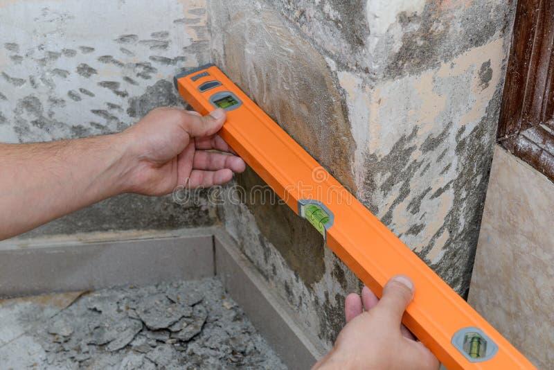 Les travaux de construction, un travailleur mesurent le mur en établissant le niveau images libres de droits