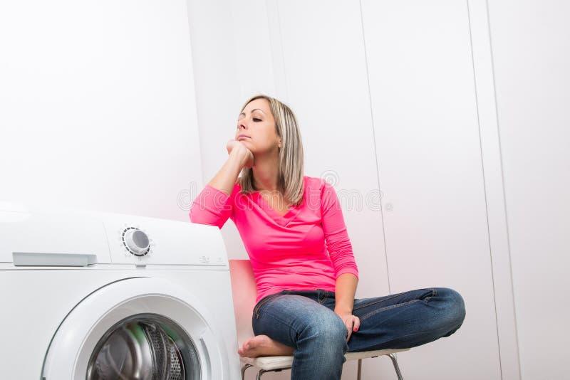 Les travaux domestiques : jeune femme faisant la blanchisserie image libre de droits