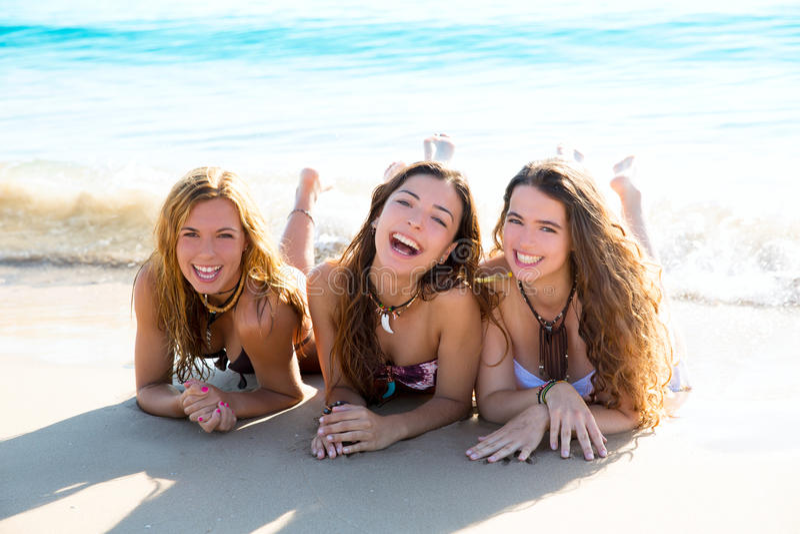 Les trois filles heureuses d'amis se trouvant sur la plage poncent le sourire images libres de droits