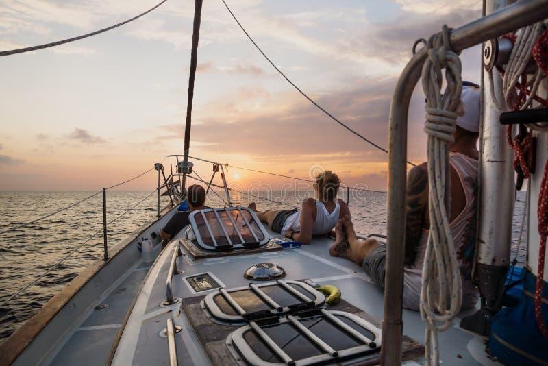 Les trois jeunes appréciant le coucher du soleil sur l'avant d'un voilier au Honduras, Amérique Centrale image stock