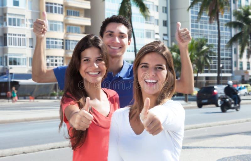 Les trois jeunes dans la ville montrant le pouce  photos stock