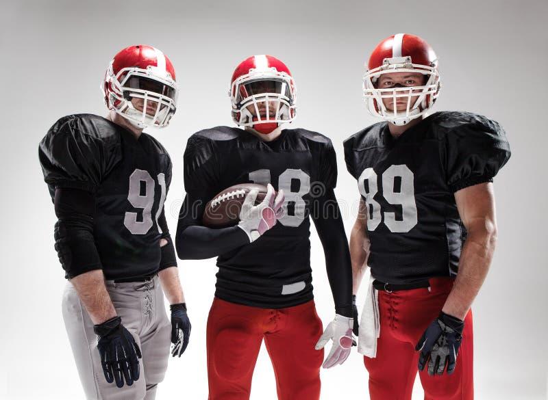 Les trois joueurs de football américain posant avec la boule sur le fond blanc photographie stock libre de droits