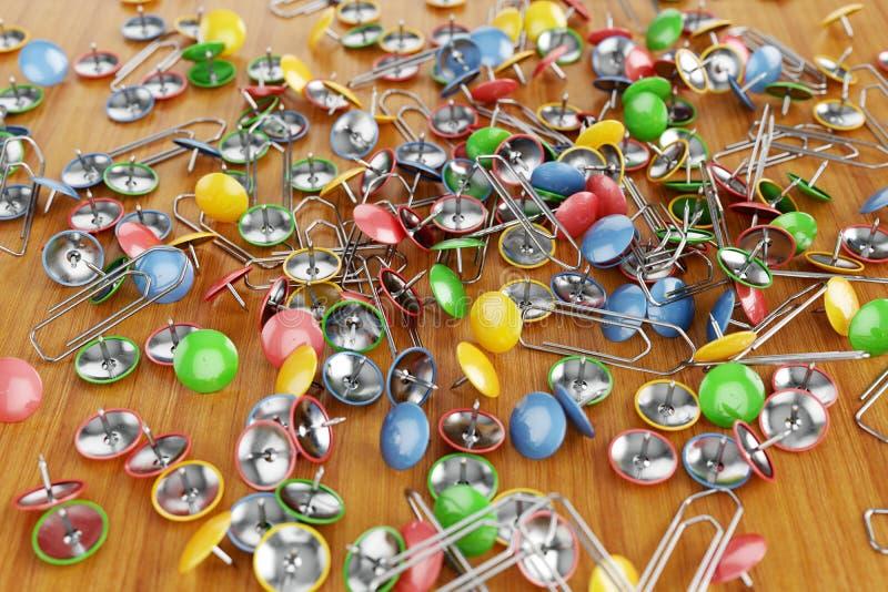 Les trombones colorés de bureau et les goupilles de dessin ont dispersé sur une table illustration stock