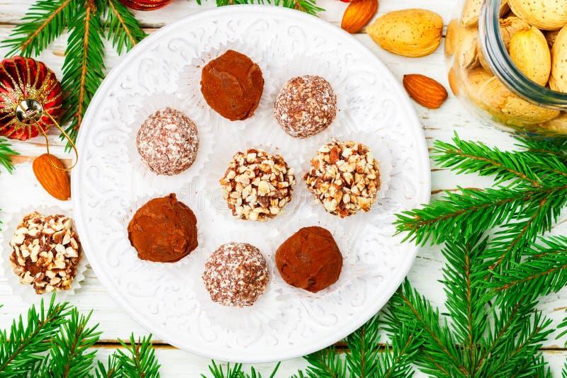 Les truffes de chocolat faites maison avec les amandes, la noix de coco et les biscuits panent dans un plat blanc images libres de droits