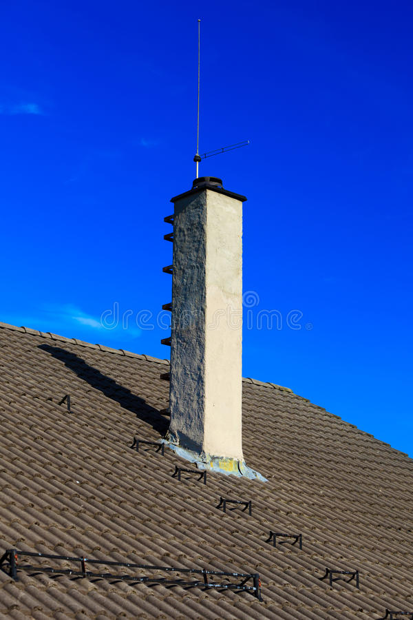 Les tuiles de toiture logent le toit avec le fond de ciel de cheminée image stock