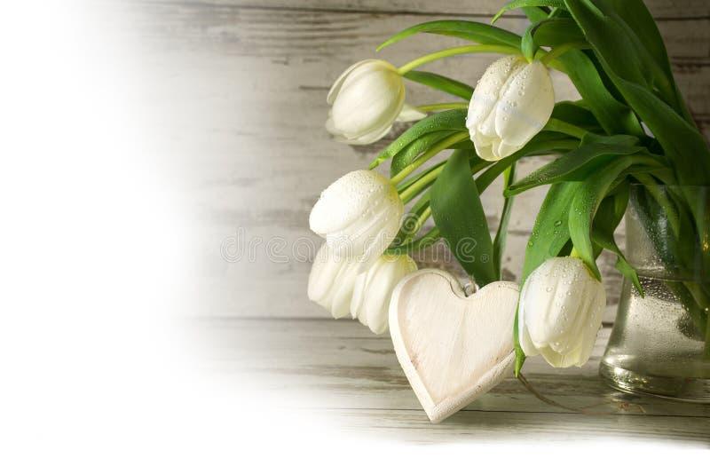 Les tulipes blanches et un coeur en bois forment contre le bois gris, coin photos libres de droits
