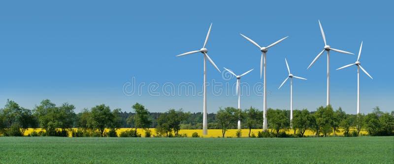 Les turbines de vent dans une graine de colza mettent en place derrière une ruelle photos libres de droits