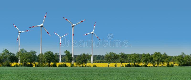 Les turbines de vent dans une graine de colza mettent en place derrière une ruelle photo stock