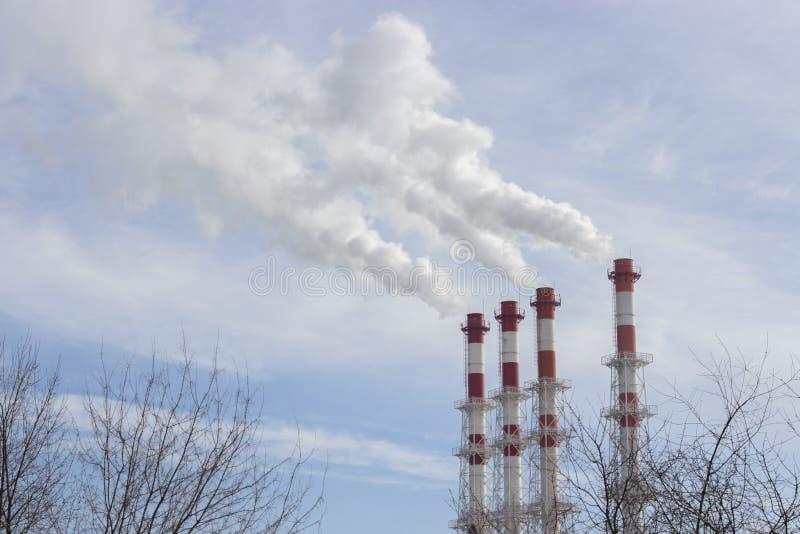 les tuyaux blanc rouge déchargent la fumée blanche de vapeur dans un ciel bleu lumineux photo stock