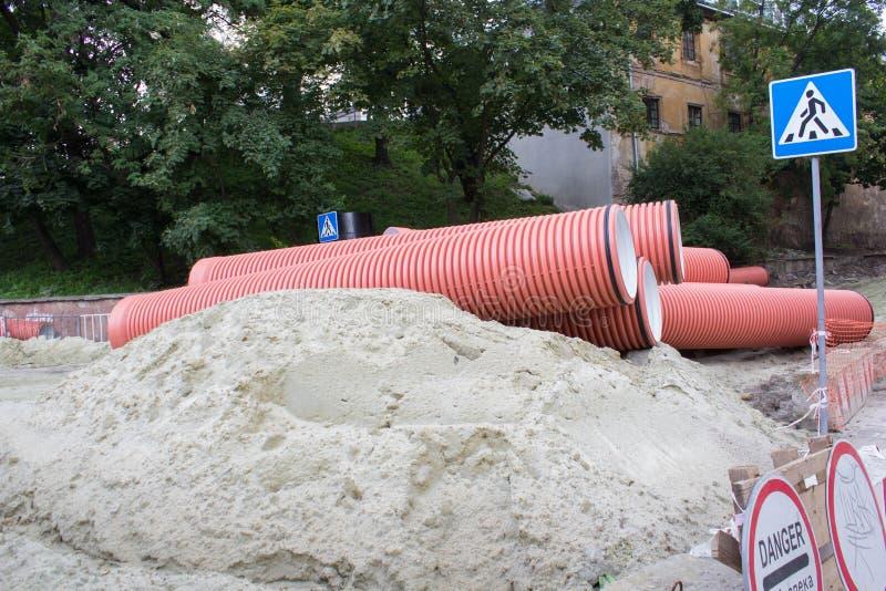 Les tuyaux d'eaux d'égout sur le sable, réparent la rue dans la ville beaucoup de sable avec des tuyaux d'eaux d'égout image stock