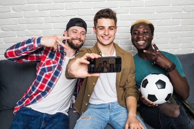 Les types attirants boivent de la bière, faisant le selfie à l'aide du téléphone et souriant tout en se reposant sur le divan à l image libre de droits