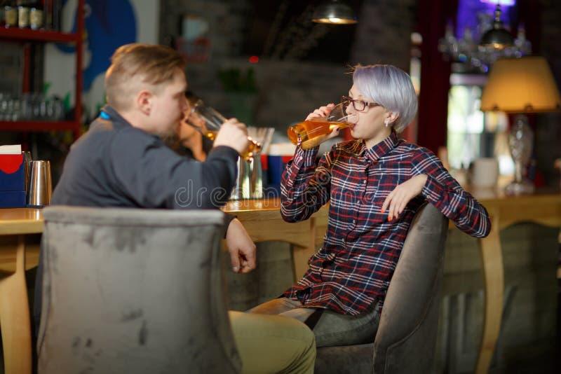 Les types et une fille boivent de la bière se reposant dans une barre indoors image stock