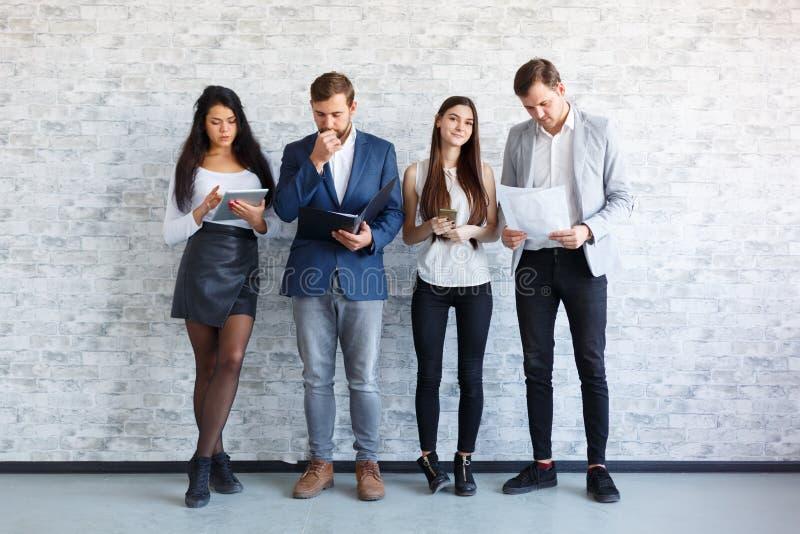 Les types et une fille sont tenants et tenants le document, le dossier, un comprimé et des téléphones indoors image stock