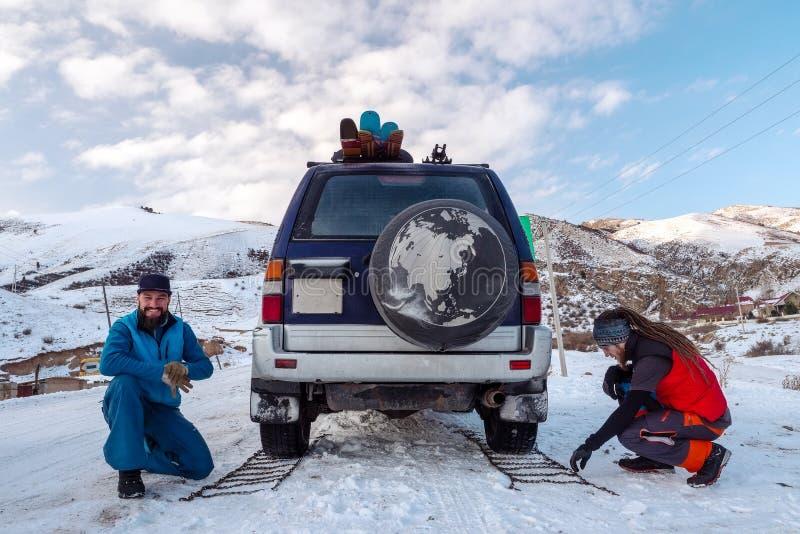 Les types ont placé sur des chaînes pour pneumatiques de voiture, pour conduire sur les routes glissantes images libres de droits
