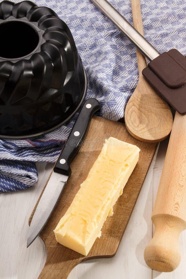 Les ustensiles de cuisson et une barre beurrent sur le conseil en bois photo stock