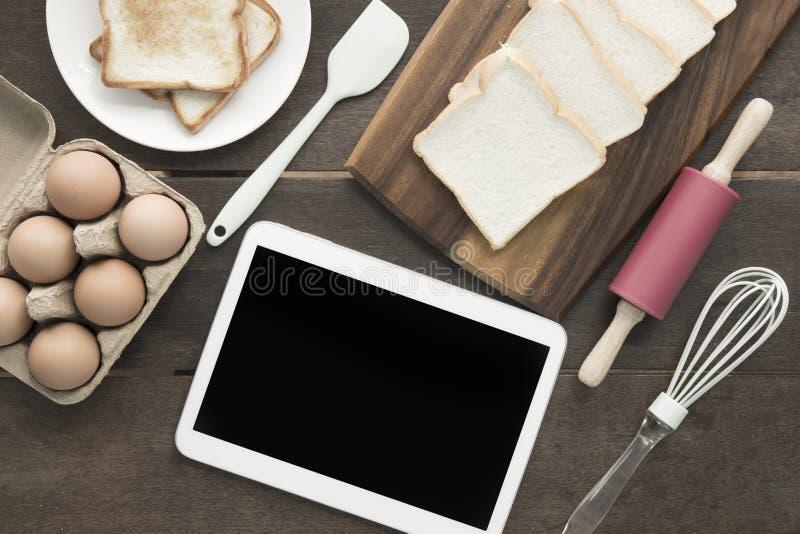 Les ustensiles outil de cuisson et le chemin de coupure de comprimé d'oeufs à l'écran rouissent photo stock