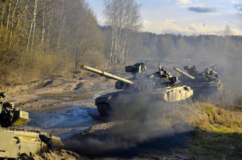 Les véhicules blindés de combat russes dirigent par le marécage par des forêts photos stock