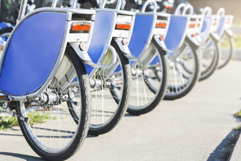 Les vélos semblables bleus se tiennent sur le stationnement pour le loyer images libres de droits