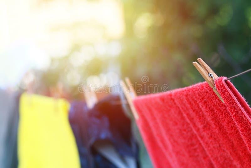 Les vêtements accrochant sur une corde à linge sèchent dehors photos libres de droits