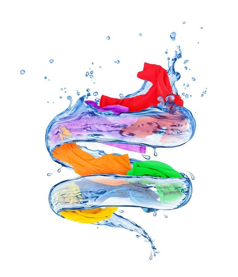 Les vêtements colorés tourne dans un remous de l'eau sur le fond blanc image stock