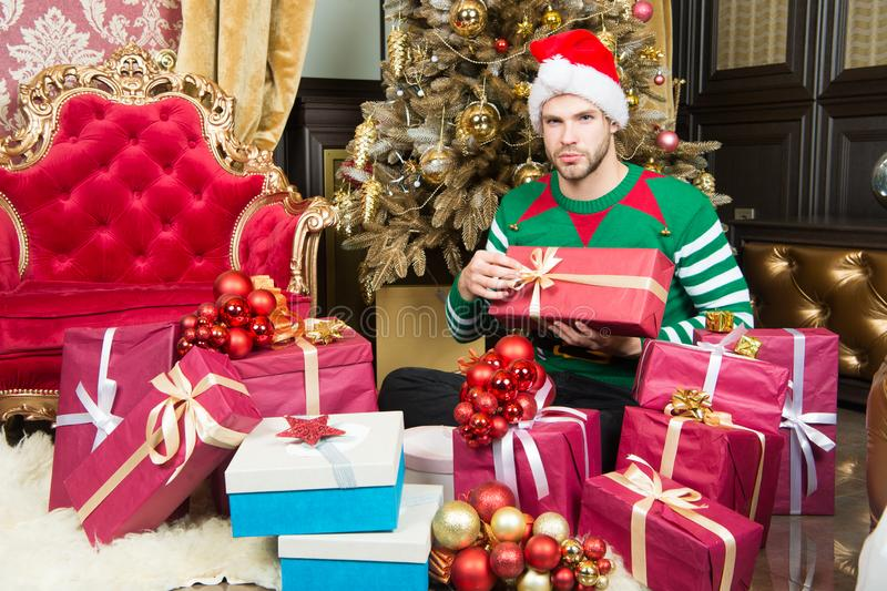 Les vêtements d'elfe de chapeau de Santa d'usage d'homme célèbrent l'arbre et les cadeaux de sapin décorés intérieurs de Noël Tem photo libre de droits