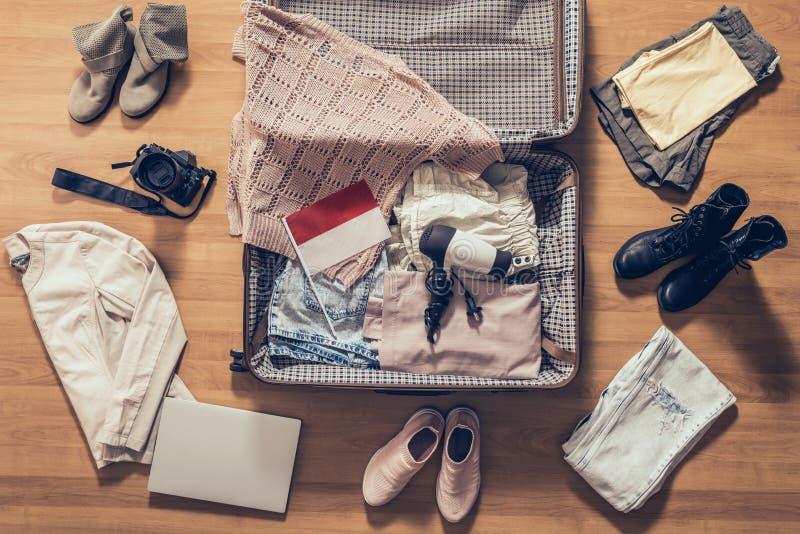 Les vêtements de la femme, l'ordinateur portable, le camer, le passeport russe et le drapeau de l'Indonésie se situant sur le pla photographie stock libre de droits