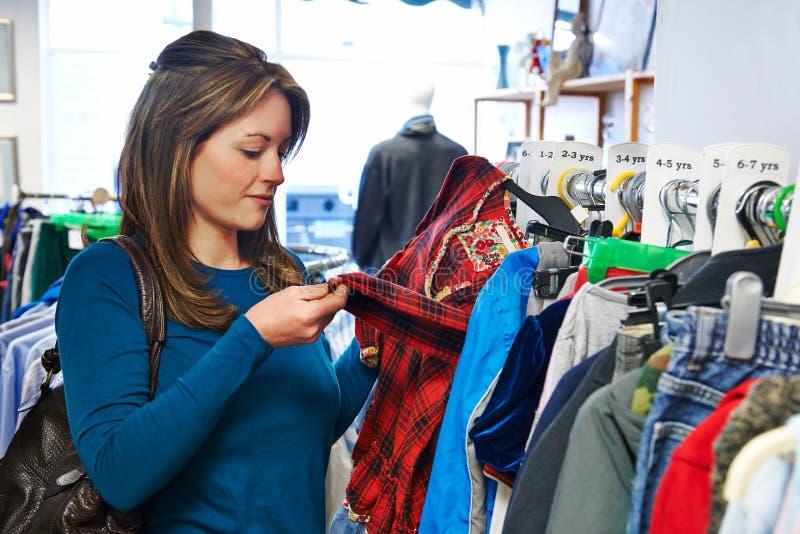 Les vêtements des enfants de achat de femme dans la boutique de charité photos stock