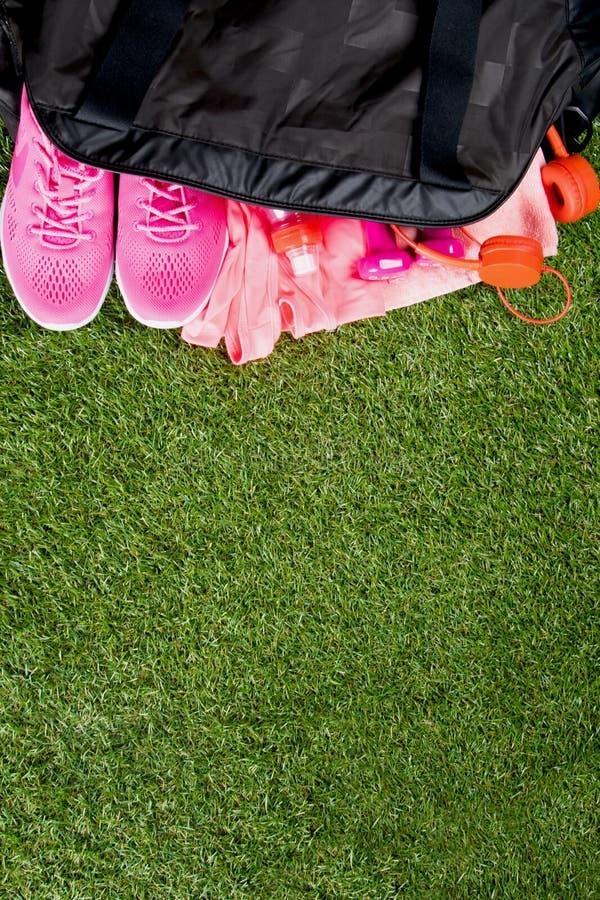 Les vêtements et les accessoires roses pour la forme physique, une bouteille de l'eau, dans des sports noirs mettent en sac, sur  photo stock