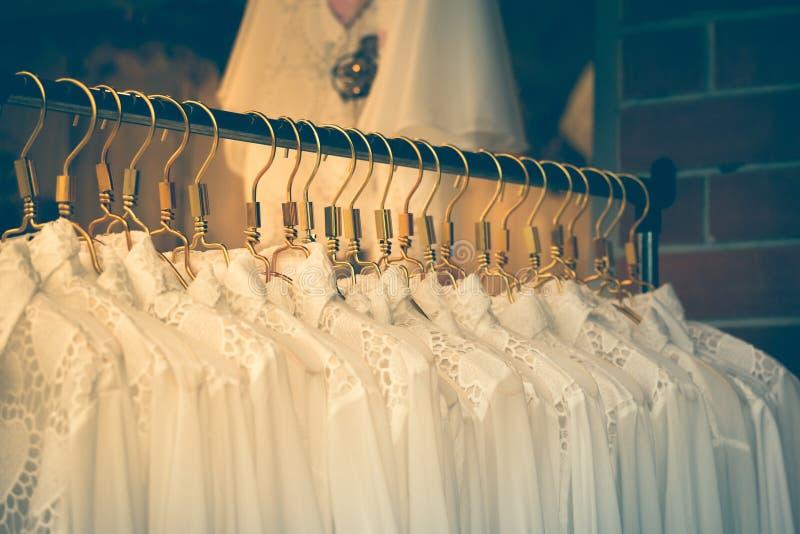 Les vêtements façonnent sur des cintres au magasin d'habillement Avec le filtre de vintage photos libres de droits