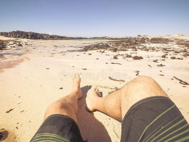 Les vacances d'été au concept de plage avec le point de vue alternatif des jambes de l'homme et le sable - détendez et appréciez  photo libre de droits