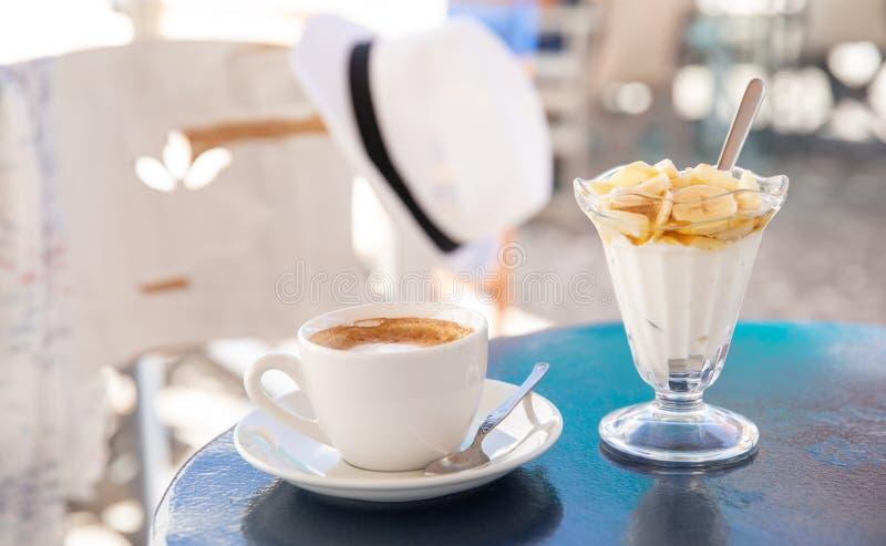 Les vacances d'été légères et savoureuses déjeunent chapeau de cappuccino de café et le yaourt avec la banane coupée en tranches, photographie stock