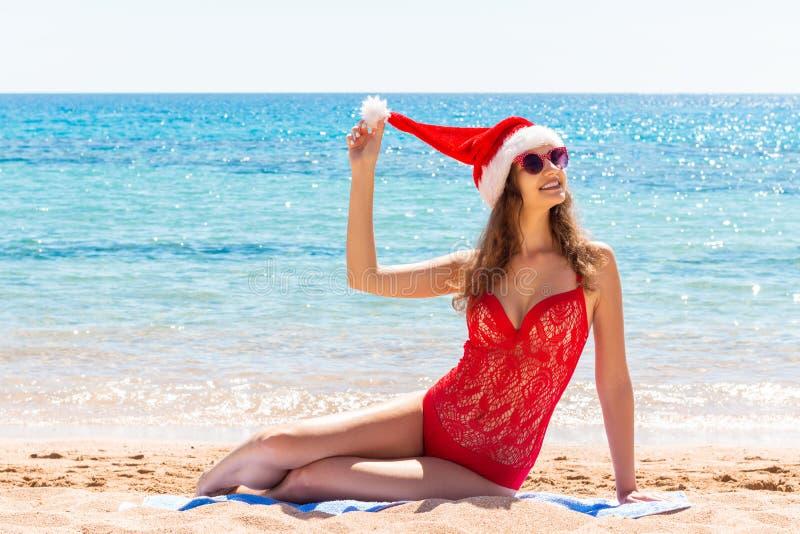 Les vacances de Noël sur la fille de la côte A dans un maillot de bain et un chapeau rouges de Santa Claus se reposent sur une pl image stock