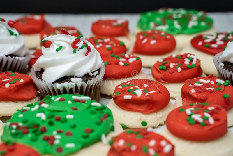 Les vacances de Noël traitent - les petits gâteaux et les biscuits de sucre de buttercream avec arrose photo stock