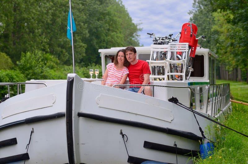 Les vacances romantiques, voyage sur le bateau de péniche, les couples heureux sur la rivière croisent dans le bateau-maison photos libres de droits