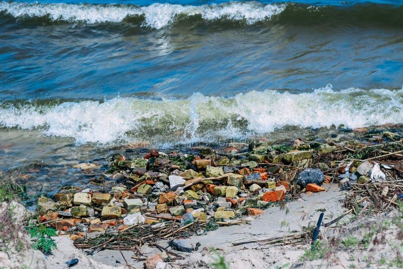 Les vagues apportent des pierres et des débris de bâtiment au rivage image libre de droits