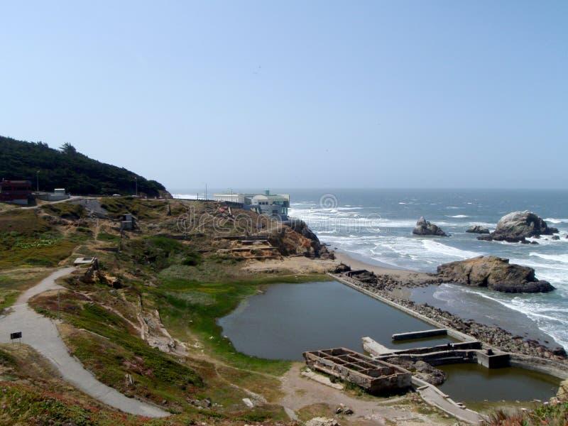 Les vagues roulent vers le rivage de la plage d'océan avec Cliff House et les ruines de la Chambre de Bath de Sutro dans le premi images libres de droits