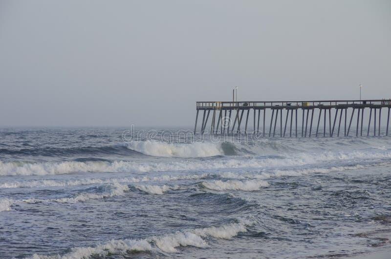 Les vagues se brisent sur le pilier une soirée orageuse, ville d'océan, Marylan photo stock