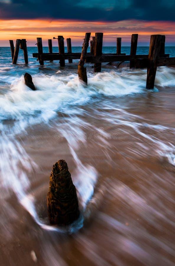 Les vagues tourbillonnent autour des empilages de pilier dans la baie de Delaware au coucher du soleil, s image stock
