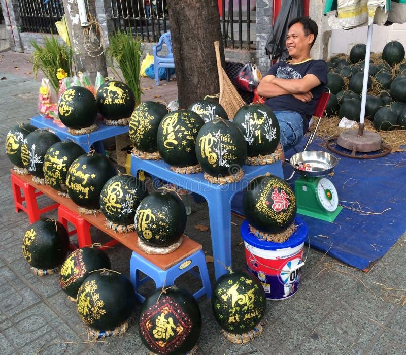 Les ventes d'homme ont gravé des pastèques pour Tet (nouvelle année lunaire dans Vietn image libre de droits