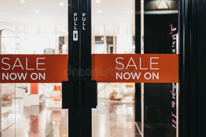 Les ventes se connectent maintenant dessus une porte de magasin photographie stock