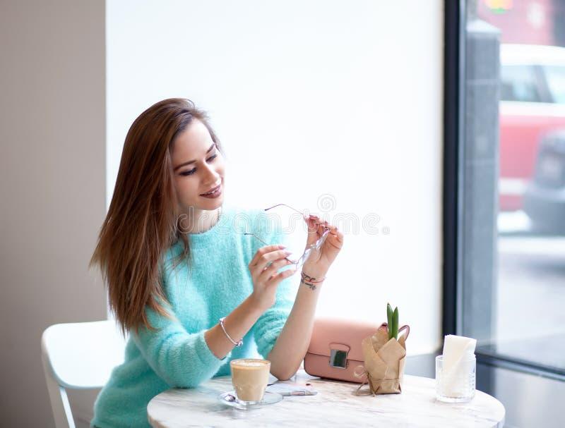 Les verres beaux de whith de jeune femme semblant la participation partie téléphonent tout en chillling en café photo libre de droits