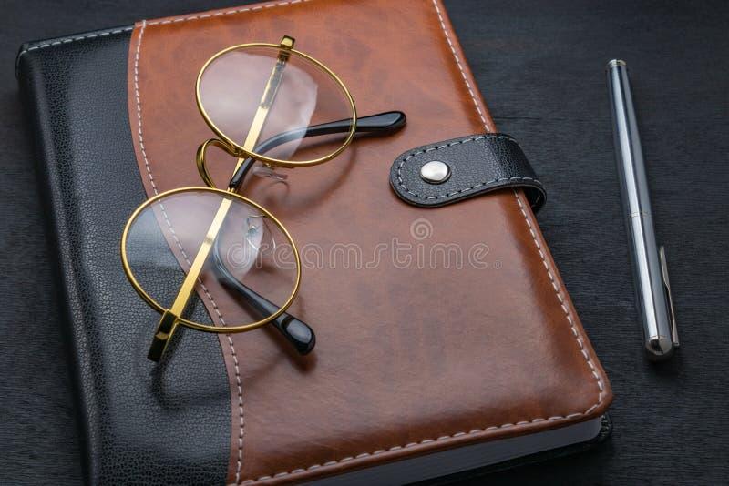 Les verres, bloc-notes, stylo s'étendent sur une table foncée photos stock